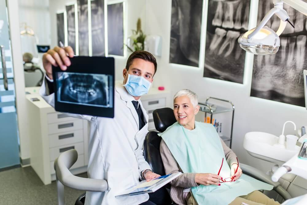 older dental patient review dental x-rays with dentist