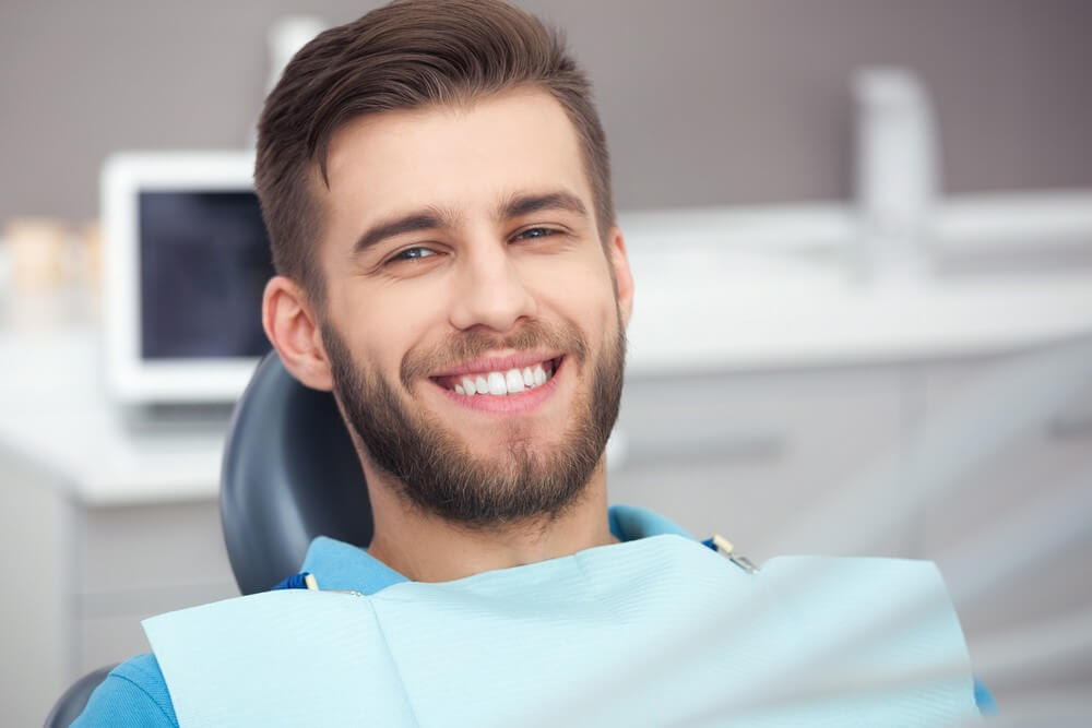 male adult smiling, anticipating a wisdom tooth removal