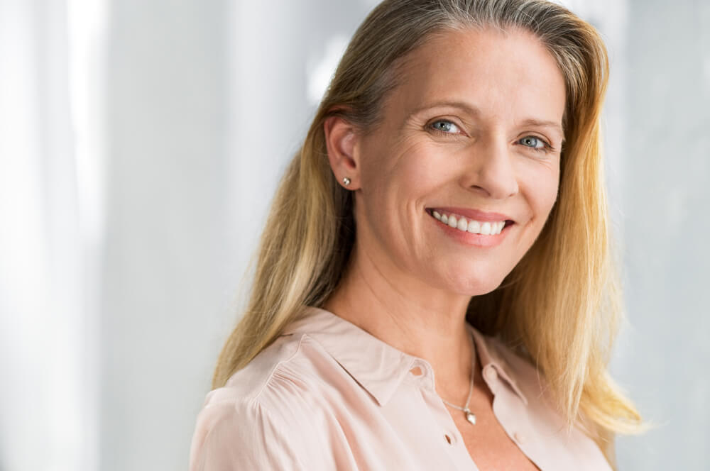 woman smiling proudly with dentures
