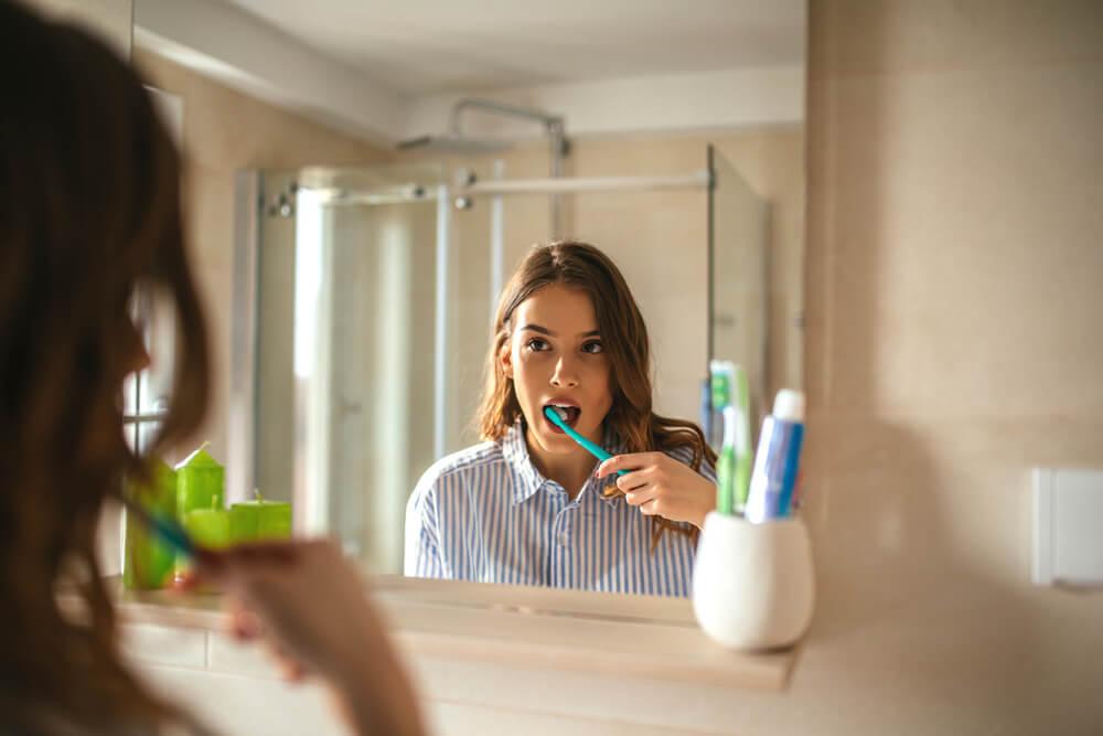 woman brushing her teeth in the bathroom mirror
